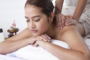 primo piano di una giovane donna che riceve il massaggio alla schiena in spa foto