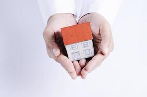 carta della casa di protezione con la mano foto