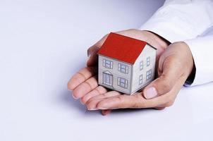 mano che tiene la carta della casa per il concetto di prestiti ipotecari foto