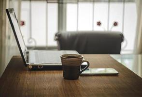 posto di lavoro aziendale con una tazza di caffè smartphone e laptop. foto