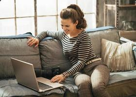 donna con la macchina fotografica del dslr che utilizza computer portatile nell'appartamento del sottotetto foto