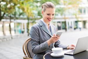 donna di affari che per mezzo del computer portatile al caffè foto