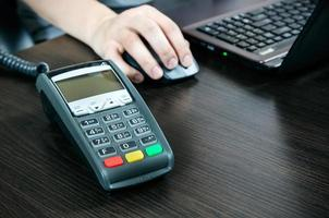 terminale di pagamento in ufficio. laptop in background foto