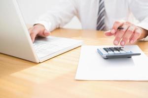 un uomo d'affari alla sua scrivania utilizzando un computer e una calcolatrice foto