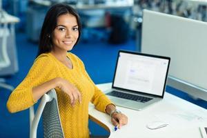 donna di affari allegra che si siede al tavolo con il computer portatile foto