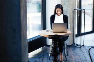 donna di affari felice che utilizza computer portatile nel caffè foto