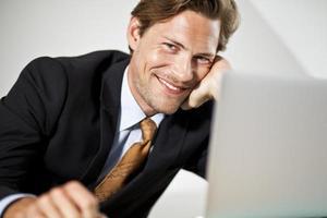 uomo d'affari caucasico sorridente che per mezzo del computer portatile foto