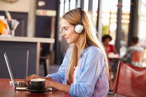 giovane donna che utilizza il computer in un bar foto