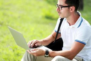 studente di college che studia per mezzo del computer portatile foto