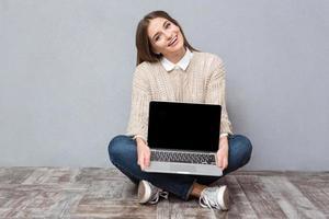 ragazza allegra che si siede sul pavimento e che tiene lo schermo in bianco del computer portatile foto