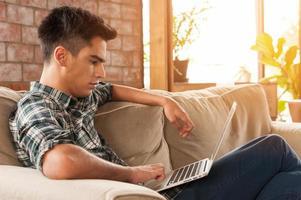 uomo d'affari che utilizza computer portatile sul sofà nella caffetteria foto