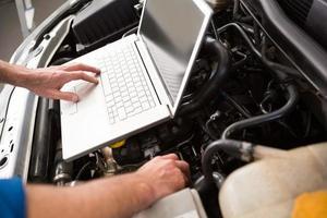 meccanico che per mezzo del computer portatile sull'automobile foto