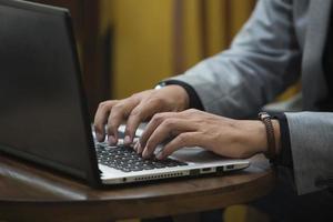 mani che digitano sul computer portatile foto