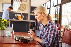 donna che per mezzo del computer portatile ad una caffetteria