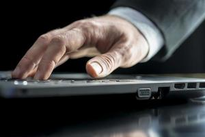 uomo d'affari digitando su un computer portatile