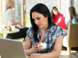 donna che utilizza computer portatile nel caffè foto