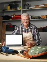 carpentiere in pensione con laptop foto