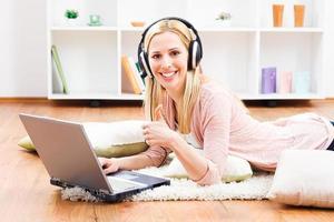 donna con le cuffie che per mezzo del computer portatile foto