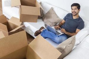 uomo asiatico che per mezzo del computer portatile che disimballa le scatole che muovono casa foto