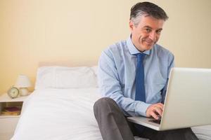 uomo contento che per mezzo del suo computer portatile che si siede su un letto
