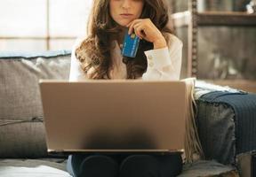 primo piano sulla donna con la carta di credito che utilizza computer portatile nell'appartamento foto