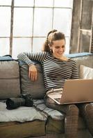 giovane donna sorridente con la macchina fotografica moderna del dslr che per mezzo del computer portatile foto