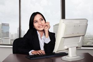 donna felice sorridente che per mezzo del computer foto