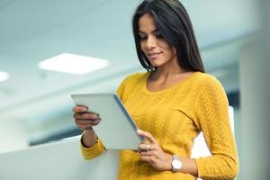 donna di affari che utilizza il computer della compressa nell'ufficio foto