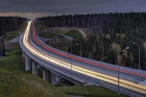 sentieri di luce sull'autostrada a quattro corsie, attraversa la foresta di notte.