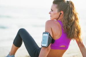 giovane donna di forma fisica che si siede sulla spiaggia. retrovisore foto