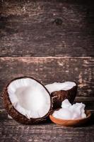noci di cocco e olio sul tavolo di legno foto
