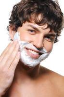bell'uomo applicando la crema da barba sul viso foto