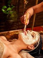 una donna sdraiata in un asciugamano che indossa una maschera presso la spa ayurveda foto