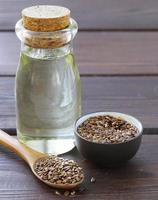 olio di semi di lino in bottiglia di vetro su un tavolo di legno foto