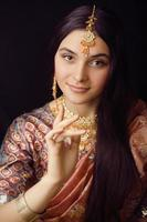 ragazza indiana dolce di bellezza in sari che sorride vicino in su foto