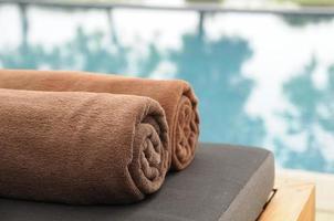 asciugamano arrotolato posto sul letto accanto alla piscina. foto