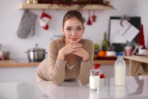 sorridente giovane donna che beve latte, in piedi in cucina foto