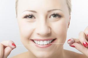 donna caucasica filo interdentale denti e sorridente foto