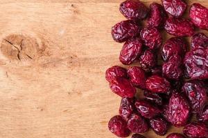 dieta cibo sano. bordo di mirtilli rossi secchi su fondo di legno foto