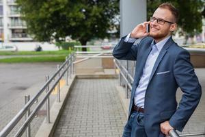 uomo d'affari caucasico fuori ufficio utilizzando il telefono cellulare.
