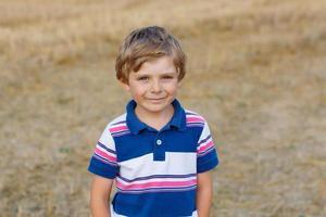 ragazzo caucasico del bambino di cinque anni sul campo di fieno