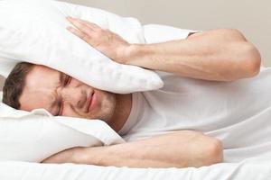 Ritratto di giovane uomo caucasico insoddisfatto nel letto foto