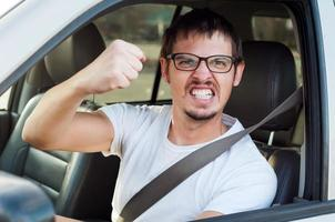 maschio caucasico arrabbiato pazzo driver sta mostrando il pugno