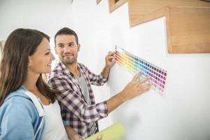 giovane coppia scegliendo il colore della vernice e carta pent