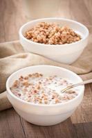 Porridge di grano saraceno con latte su un tavolo di legno foto