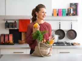 donna che ride, caduta frutta e verdura in cucina foto