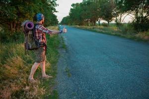 giovane turista caucasico autostop lungo una strada