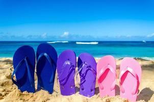 infradito colorate sulla spiaggia di sabbia foto