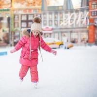 adorabile bambina felice godendo pattinaggio presso la pista di pattinaggio