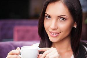 la ragazza graziosa sta godendo della bevanda calda nel self-service foto